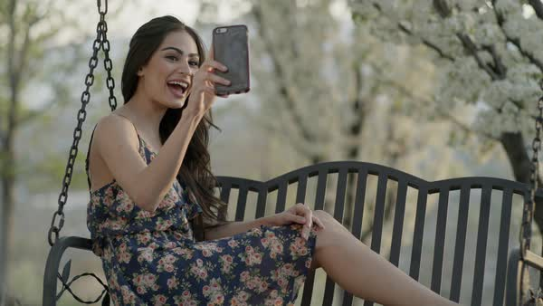 Medium slow motion shot of woman video chatting on bench swing Royalty-free stock video