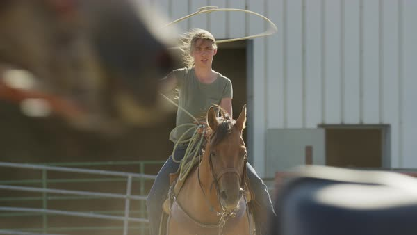 Medium slow motion shot of girl spinning lasso on horse Rights-managed stock video