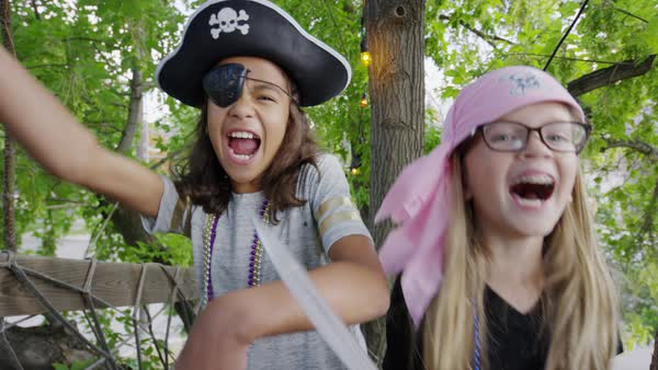 Close up of girls holding swords playing pirate in tree / Provo, Utah, United States Royalty-free stock video