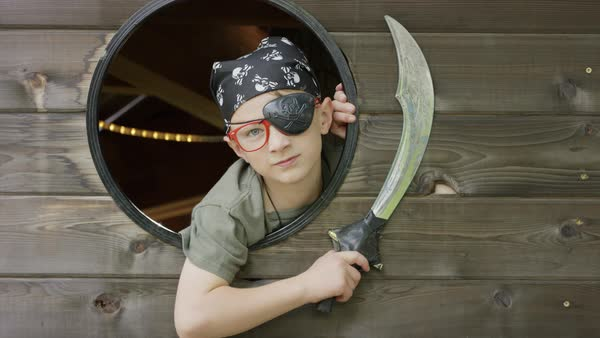Close up of fierce boy playing pirate in window with swords / Provo, Utah, United States Royalty-free stock video