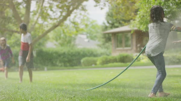 Girl with garden hose spraying friends running in grass / Provo, Utah, United States Royalty-free stock video