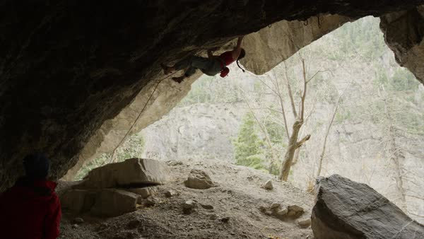 Slow motion of spotter watching woman rock climbing on ceiling of cave Rights-managed stock video