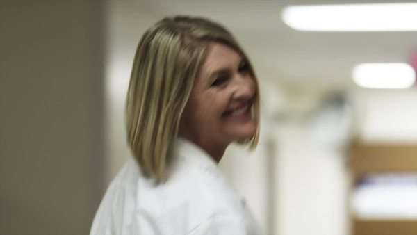 Slow motion medium shot female doctor smiling in corridor / Payson, Utah, USA Rights-managed stock video