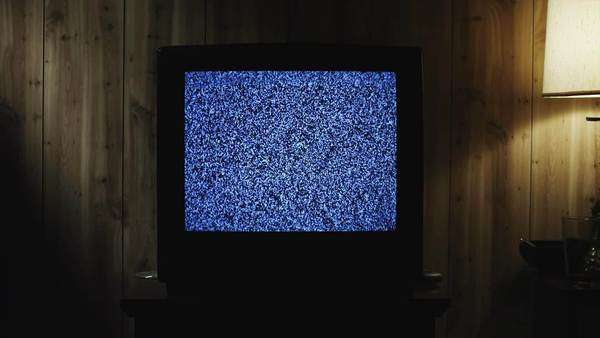 Medium shot zoom in extreme close up television static on TV set in living room / Orem, Utah, USA Rights-managed stock video