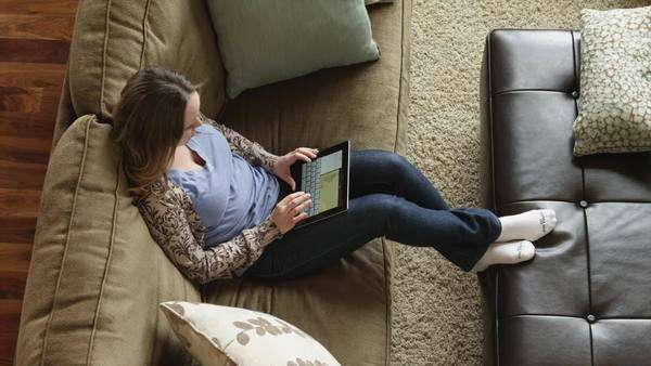 High angle medium shot Young woman using digital tablet, sitting on sofa / Lehi, Utah, USA Rights-managed stock video