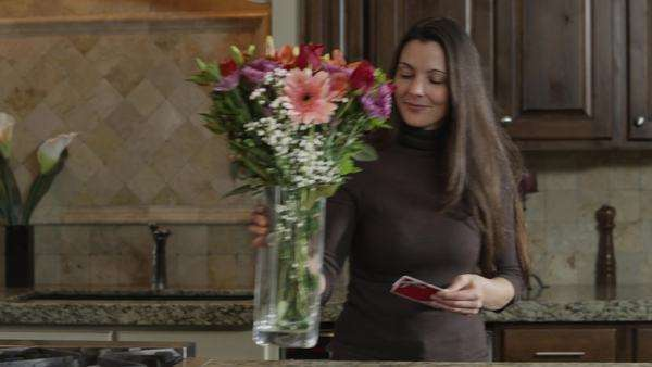 MS DS Woman carrying vase of flowers and reading card  Royalty-free stock video