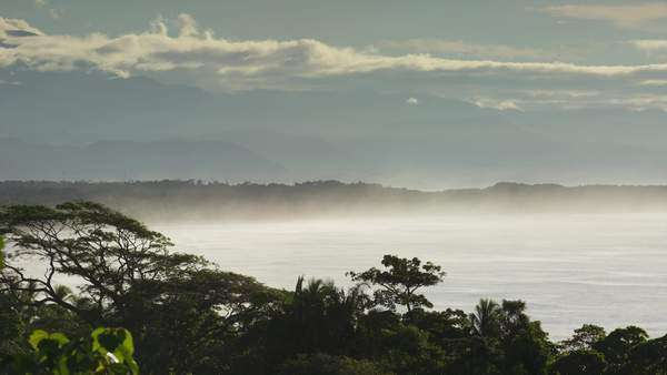 Wide shot of mist over ocean under cloudy sky / Esterillos, Puntarenas, Costa Rica Royalty-free stock video