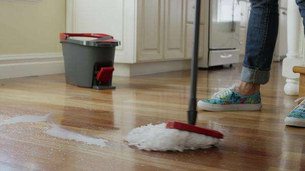 low angle medium panning shot of woman mopping kitchen floor