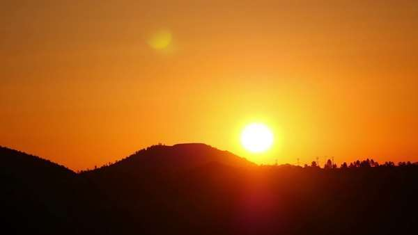 Wide angle timelapse sunrise of bright sun over hill in bright red sky. timelapse Royalty-free stock video