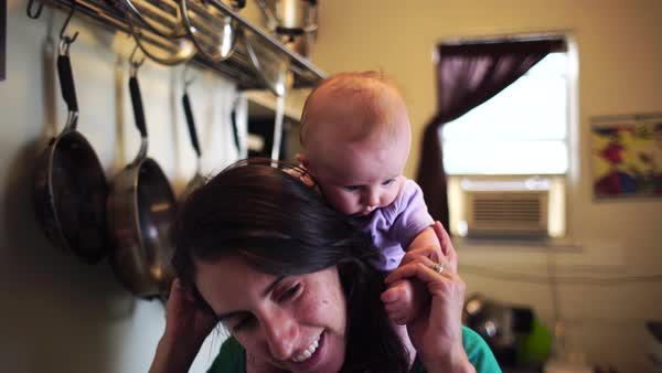 Medium close-up shot of a mother and her baby in a kitchen Royalty-free stock video