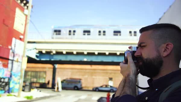 Close-up of young man snapping a photo with train in the background Royalty-free stock video