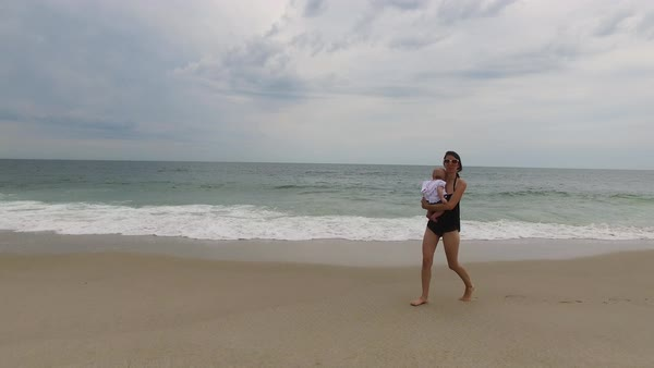 Tracking wide shot of mother walking on beach Royalty-free stock video
