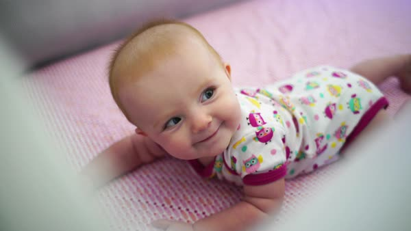 Hand-held close-up of playful baby girl in bed Royalty-free stock video