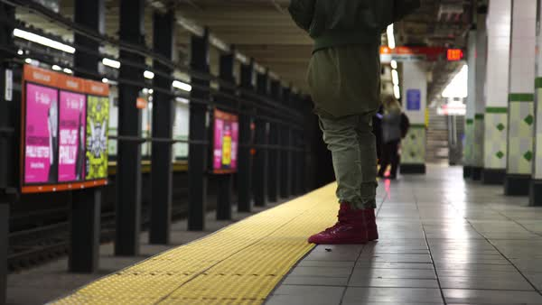 Hand-held shot of man standing at a subway station Royalty-free stock video