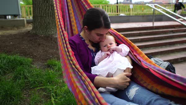 Medium shot of a woman relaxing in a hammock with a baby girl Rights-managed stock video