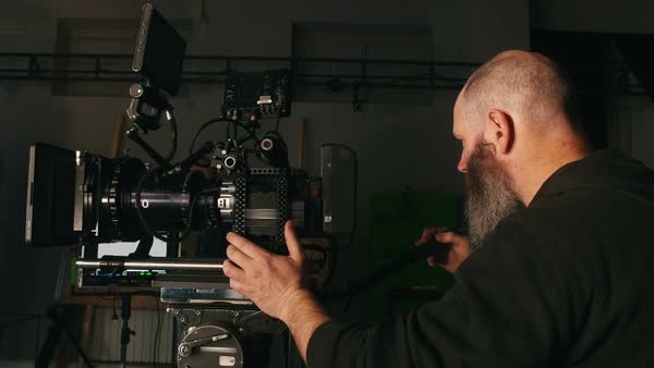 Camera operator waiting for cue on pan shot in studio environment Royalty-free stock video