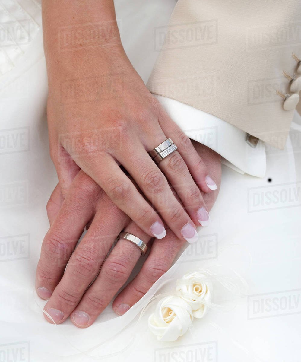 Hand of bride and groom with wedding rings - Stock Photo - Dissolve