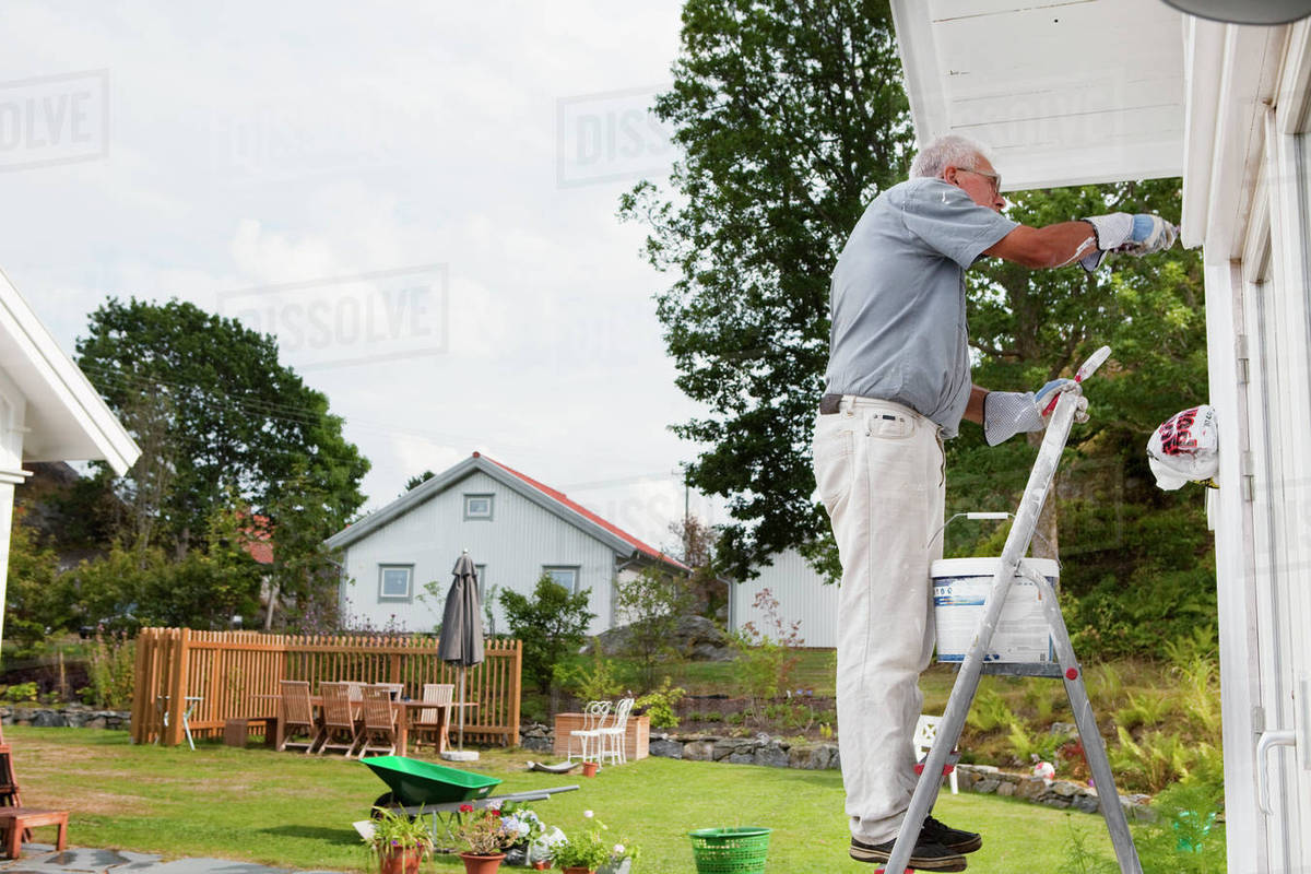 Senior man painting house stock photo