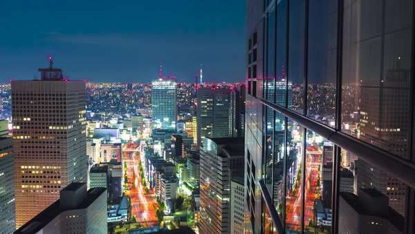 Timelapse Tokyo from atop a skyscraper at night in Shinjuku, Tokyo, Japan. The windows of the building create reflections of the traffic below. Royalty-free stock video