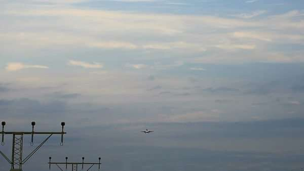 Large jet airplane is flying over runway approach lights at