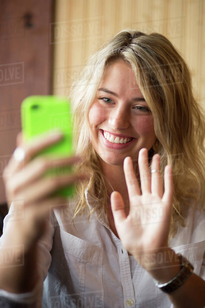 Selective focus close up of happy woman waving at cell phone and video chatting Royalty-free stock photo