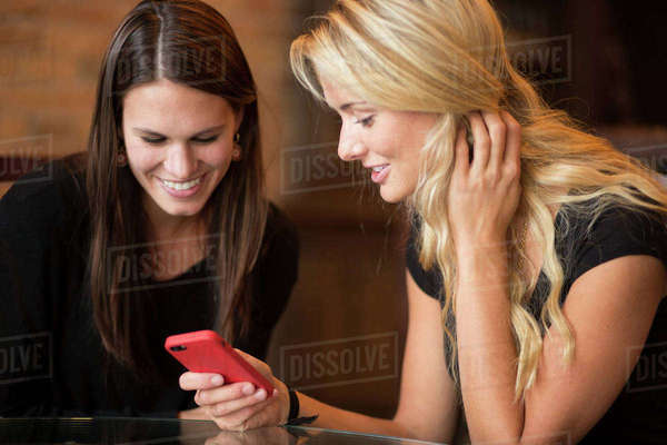 Women with long hair looking down sharing cell phone at table Royalty-free stock photo