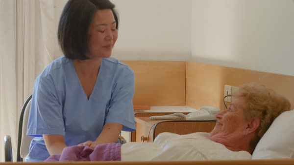 Nurse reassuring elderly female patient in hospital bed. Royalty-free stock video