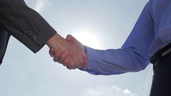 Slow motion of businessmen shaking hands, backlit Royalty-free stock video