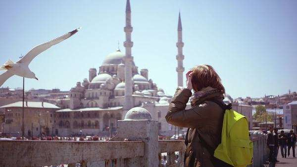 SLOW MOTION: pretty girl in Istanbul looks at the harbour and mosque. A big seagull flies by all of a sudden and the girl is really surprised. Royalty-free stock video