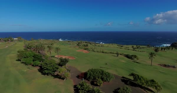 Aerial shot over golf field by the ocean. Blue skies and clouds. Royalty-free stock video