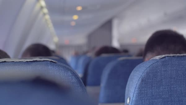 Passenger airplane cabin during the flight. Men and women are sitting in the passenger seats, the view from the back Royalty-free stock video