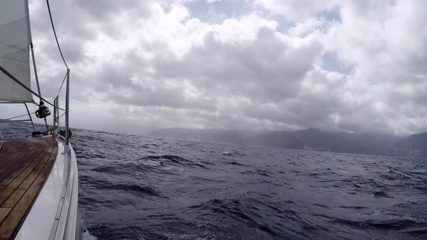 Sailing yacht approach the shore with a mountainous terrain in cloudy weather. Journey on a yacht. Gray sky with low storm clouds, gloomy sea Royalty-free stock video