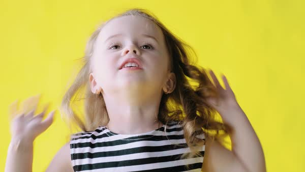 721a8d785 Portrait of a cute beautiful little girl with long curly hair on a yellow  background,