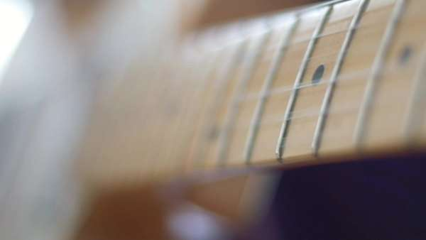 Caucasian man plays solo on guitar in slow motion. Macro shot with rack focus. Royalty-free stock video