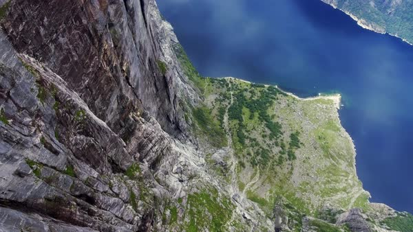 Top view of the coastline along clean beautiful blue river, huge cliffs. Rotate the camera around its axis. Magnificent panoramic view of the reservoir, pond with clear water and rocks. Norway, Europe Royalty-free stock video