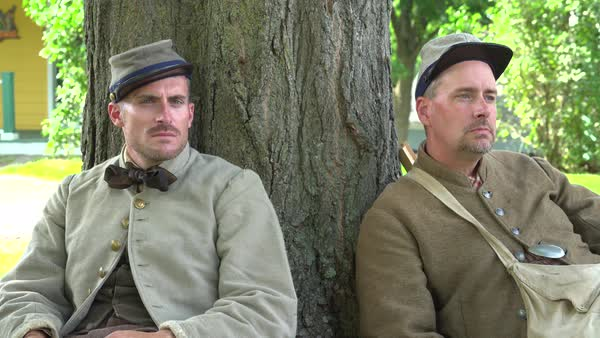 View of Two tired Civil War soldiers resting by tree Royalty-free stock video