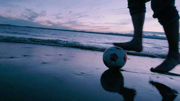 Man dribbles soccer ball in front of waves at sunset Royalty-free stock video