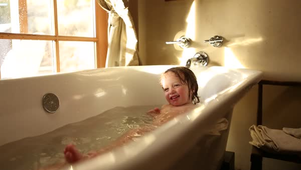 2 year old toddler boy playing in bath tub with his 9 year old ...