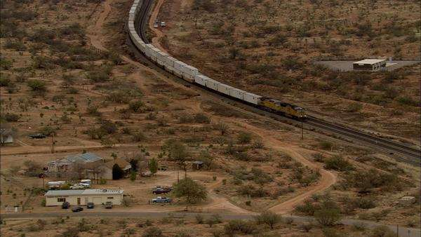 Desert Train Through Mountains  An aerial, sweeping view of