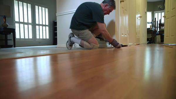 A homeowner handyman type removing quarter round shoe molding as part of his DIY project to replace old flooring. Royalty-free stock video