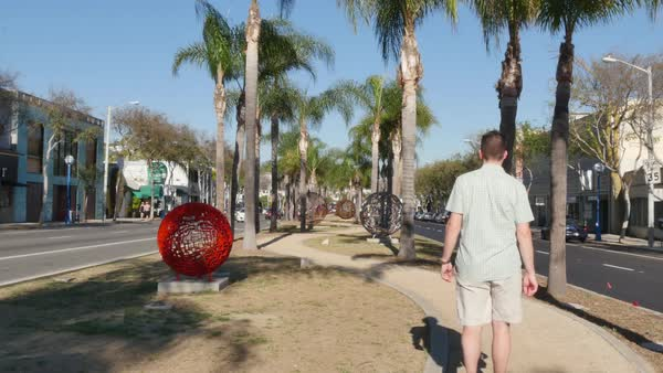 WEST HOLLYWOOD - Circa February, 2016: A man walks past sculptures in West Hollywood.  	 Royalty-free stock video