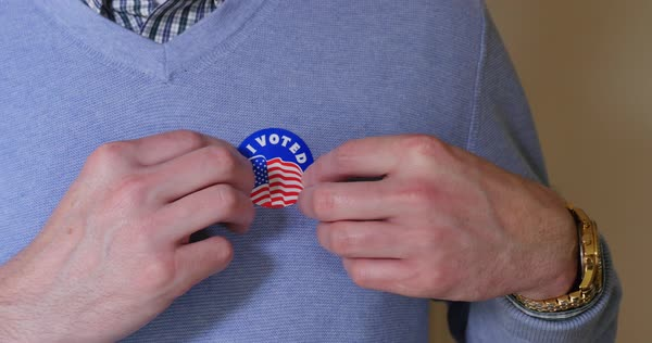 A man puts an I Voted sticker on his sweater after voting.  	 Royalty-free stock video