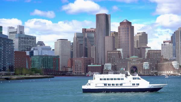 A daytime establishing shot of the Boston skyline as seen from the harbor while a ferry boat passes by. Royalty-free stock video