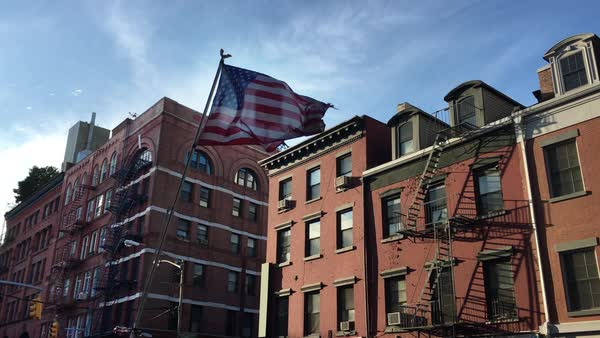 A tattered American flag flaps in the wind in front of apartment buildings in New York's Little Italy neighborhood.  	 Royalty-free stock video