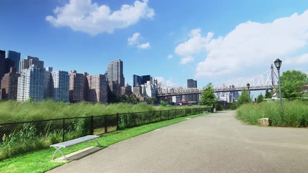 The Manhattan skyline and Ed Koch Queensboro Bridge as seen from the sidewalks and paths on Roosevelt Island.  	 Royalty-free stock video