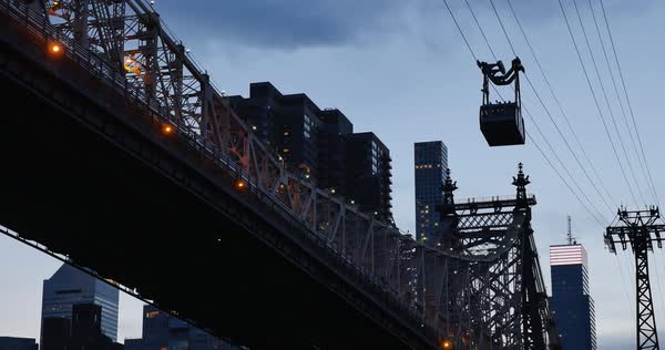 A dusk establishing shot of the Roosevelt Island Tram carrying passengers next to the Ed Koch Queensboro Bridge.  	 Royalty-free stock video
