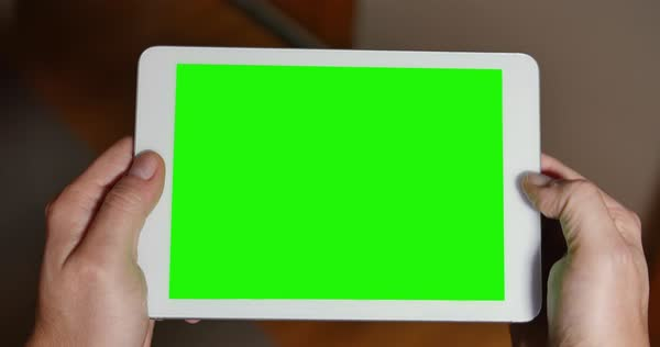 A man uses a blank green screen tablet PC to play a video game. Optional corner pin markers for advanced tracking.    Royalty-free stock video