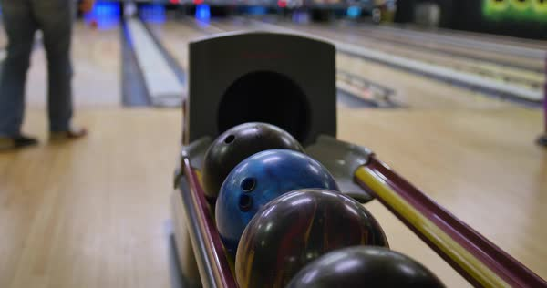 Slow tracking shot of people getting their balls from the ball return tray of a bowling alley. Extreme shallow DOF.    Royalty-free stock video