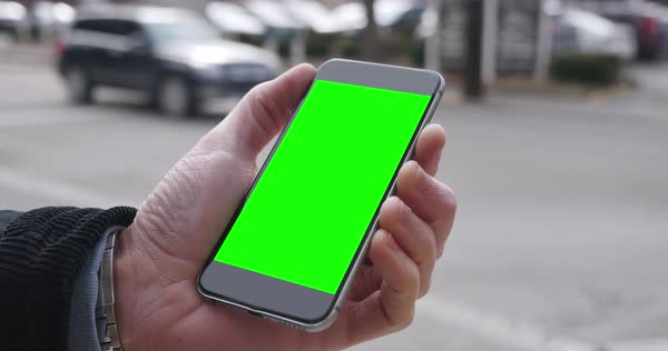 A man holding a green screen smartphone in a city	 Royalty-free stock video