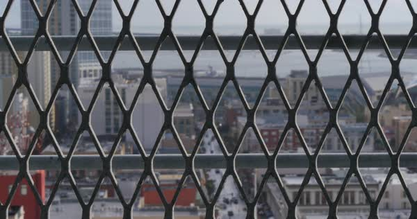 A high angle aerial abstract view of the San Diego skyline as seen through a wire fence.	 	 Royalty-free stock video